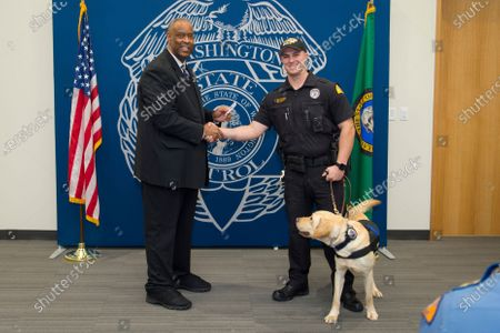 Stock Picture of In this undated photo provided by the Washington State Patrol, Trooper Justin Schaffer, right, and his K9 dog Frankie pose for a photo with WSP Chief John Batiste, left. Schaffer was killed, when he was struck by a motorist fleeing law enforcement as he attempted to deploy spike strips to bring the pursuit to a stop on Interstate 5 in Chehalis, Wash