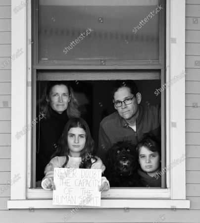 Elizabeth Parker, Tom Parker and children Clarissa and Nate and dog Gypsy pose for 'Words At The Window: Self Isolation And The Coronavirus', a portrait series by Shutterstock Staff Photographer, Stephen Lovekin, shot around the Ditmas Park neighborhood of Brooklyn, New York.