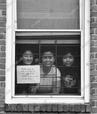 Stock Photo of Lissette Mejia, Karen Rafael, and Luz Mejia pose for 'Words At The Window: Self Isolation And The Coronavirus', a portrait series by Shutterstock Staff Photographer, Stephen Lovekin, shot around the Ditmas Park neighborhood of Brooklyn, New York.