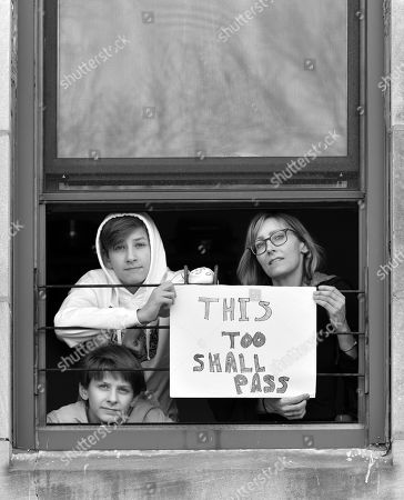 Kym O'Neill and sons Beckett Tratenberg and Grey Tratenberg pose for 'Words At The Window: Self Isolation And The Coronavirus', a portrait series by Shutterstock Staff Photographer, Stephen Lovekin, shot around the Ditmas Park neighborhood of Brooklyn, New York.