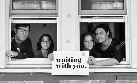 Stock Image of John and Stephanie Stislow and daughters Mira and Nona pose for 'Words At The Window: Self Isolation And The Coronavirus', a portrait series by Shutterstock Staff Photographer, Stephen Lovekin, shot around the Ditmas Park neighborhood of Brooklyn, New York.