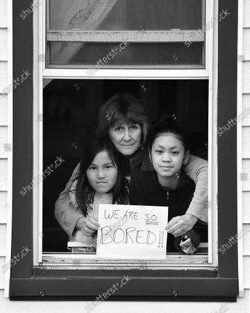 Stock Picture of Joan Adams and daughters Caitlin Ala-Toh Adams and Emma Hoi-An Adams pose for 'Words At The Window: Self Isolation And The Coronavirus', a portrait series by Shutterstock Staff Photographer, Stephen Lovekin, shot around the Ditmas Park neighborhood of Brooklyn, New York.