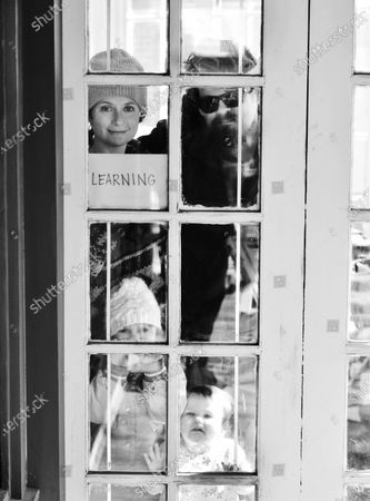 Anna Gordon and Steve Hartong and daughters Roxy and Josephine pose for 'Words At The Window: Self Isolation And The Coronavirus', a portrait series by Shutterstock Staff Photographer, Stephen Lovekin, shot around the Ditmas Park neighborhood of Brooklyn, New York.