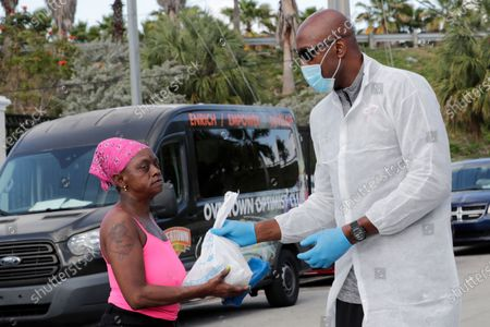 Stock Picture of Miami Heat executive Alonzo Mourning, right, hands out a breakfast and lunch package to a local resident impacted by the new coronavirus outbreak in a partnership between the Overtown Youth Center and DeliverLean, in Miami. Mourning is a founder of the Overtown Youth Center. The new coronavirus causes mild or moderate symptoms for most people, but for some, especially older adults and people with existing health problems, it can cause more severe illness or death