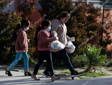 "The Gomez family twin girls, with their mother from Oaxaca, Mexico, middle, pick up ""Grab & Go"" meals provided by the Los Angeles Unified District at the Robert F. Kennedy Community School station in Los Angeles . With California virus cases surging, Gov. Gavin Newsom said his stay-at-home order for 40 million Californians may stay in place into May. Woman at left is unidentified"