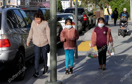 "The Gomez family twin girls, with their mother from Oaxaca, Mexico, middle, walk back home after picking up ""Grab & Go"" meals provided by the Los Angeles Unified District at the Robert F. Kennedy Community School station in Los Angeles . California virus cases surging, Gov. Gavin Newsom said his stay-at-home order for 40 million Californians may stay in place into May. Woman at left is unidentified"