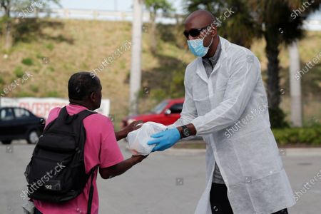 Miami Heat executive Alonzo Mourning, right, hands out a breakfast and lunch package to a local resident impacted by the new coronavirus outbreak in a partnership between the Overtown Youth Center and DeliverLean, in Miami. Mourning is a founder of the Overtown Youth Center. The new coronavirus causes mild or moderate symptoms for most people, but for some, especially older adults and people with existing health problems, it can cause more severe illness or death