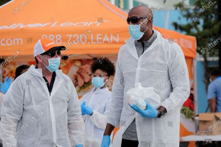 Miami Heat executive Alonzo Mourning, right, and Scott Harris, CEO of DeliverLean, left, hand out a breakfast and lunch package to local residents impacted by the new coronavirus outbreak in a partnership between the Overtown Youth Center and DeliverLean, in Miami. Mourning is a founder of the Overtown Youth Center. The new coronavirus causes mild or moderate symptoms for most people, but for some, especially older adults and people with existing health problems, it can cause more severe illness or death