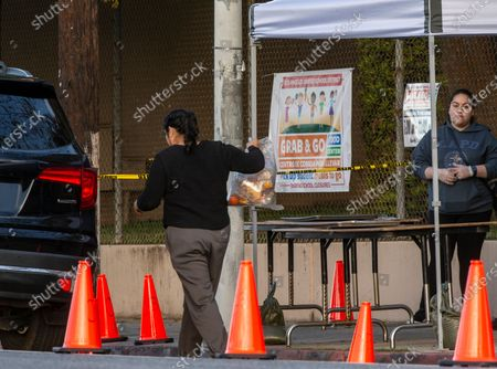 "People step out of their vehicles at a ""Grab & Go"" stop to get free school meals provided by the Los Angeles Unified District at the Virgil Middle School station in Los Angeles . As coronavirus cases surge in California, Gov. Gavin Newsom said his stay-at-home order for 40 million Californians may stay in place into May"
