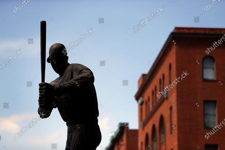 Statue of Major League Baseball hall of fame member Stan Musial stands outside Busch Stadium, home of the St. Louis Cardinals baseball team, in St. Louis. The start of the regular season, which was set to start on Thursday, is on hold indefinitely because of the coronavirus pandemic