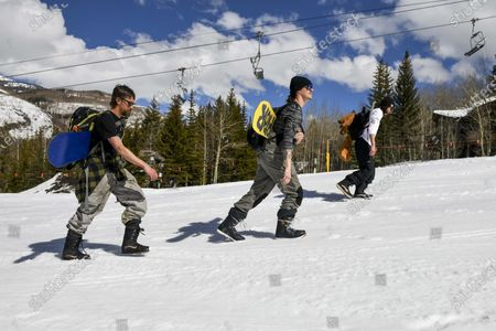 """This photo shows snowboarders, from left, Colin Tabb, Tyler Alvarez and Shaun Carroll, determined to get in a run, hike up an empty ski run past a closed chair lift at Vail, Colo., after Vail Ski Resort closed for the season amid the COVID-19 pandemic. """"Today it's desolate. It's a ghost town,"""" said Tabb, a Vail resident and snowboarder. """"Usually we are fighting lift lines and we are doing our thing still, but it's a complete ghost town"""