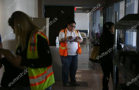 Patricia Vasquez, middle, from the U.S. Army Corps of Engineers, takes notes as she and fellow colleagues join staffers from the Arizona health department as they tour the currently closed St. Luke's Medical Center hospital to see the viability of reopening the facility for possible future use due to the coronavirus, in Phoenix