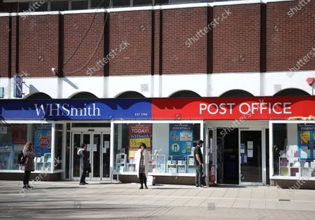 Day Two of Lockdown in Peterborough. People maintain personal distancing whilsts queueing outside the WH Smith Post Office in Peterborough.