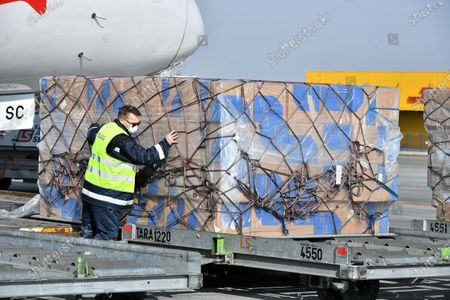 Stock Photo of Workers unload boxes with medical protective gear from China at the Frederic Chopin International Airport during the coronavirus pandemic in Warsaw, Poland, 26 March 2020. Two Polish planes carrying protective gear for Polish medical services from China, have landed in Poland on 26 March. The third plane is expected later in the day and more air deliveries are scheduled in the coming days.