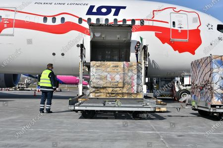 Workers unload boxes with medical protective gear from China at the Frederic Chopin International Airport during the coronavirus pandemic in Warsaw, Poland, 26 March 2020. Two Polish planes carrying protective gear for Polish medical services from China, have landed in Poland on 26 March. The third plane is expected later in the day and more air deliveries are scheduled in the coming days.