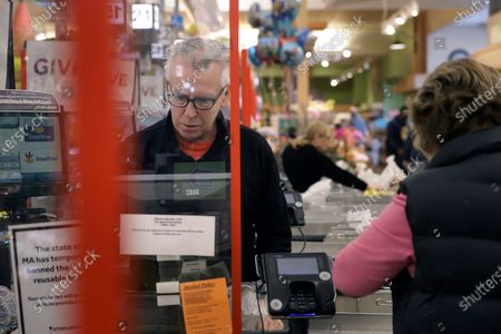 Cashier George Wallace, of Quincy, Mass., center, works while standing behind a plastic shield, at the checkout in a grocery store, in Quincy, Mass. Grocery stores across the U.S. are installing protective plastic shields at checkouts to help keep cashiers and shoppers from infecting each other with the coronavirus. The new coronavirus causes mild or moderate symptoms for most people, but for some, especially older adults and people with existing health problems, it can cause more severe illness or death