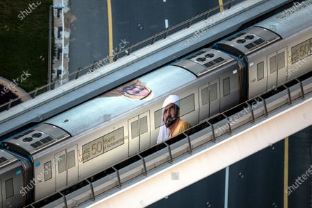 A metro bearing photograph of Sheikh Mohammed bin Rashid Al Maktoum, the Vice President and Prime Minister of the UAE, passes in Dubai, United Arab Emirates, 26 March 2020. The Ministry of Health and Community Protection and the Ministry of Interior announced on 26 March a three-day national sterilization program to limit the spread of the covid-19 coronavirus. Public traffic, transportation and metro services will be suspended, while citizens were asked to stay home as authorities sanitize all public facilities, streets and  public transportation services.