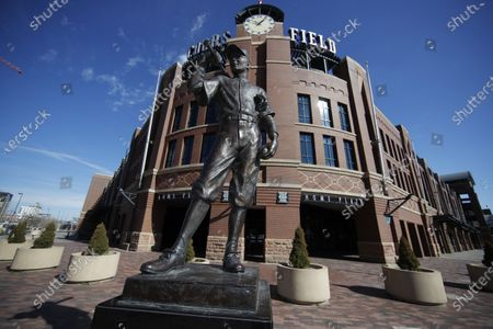 """Scuplture entitled """"The Player"""" by George Lundeen stands outside the main entracne to Coors Field, home of Major League Baseball's Colorado Rockies, as the sidewalks stand empty on the league's scheduled opening day for the 2020 season with a statewide stay-at-home order taking effect to reduce the spread of the new coronavirus, in Denver. The new coronavirus causes mild or moderate symptoms for most people, but for some, especially older adults and people with existing health problems, it can cause more severe illness or death"""
