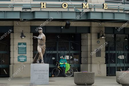 Stock Picture of Al Jackson, a die-hard Seattle Mariners fan and 11-year season ticket holder, leans against the gate at the home plate entrance near the Ken Griffey Jr. statue at T-Mobile Park in Seattle, around the time when the Mariners' Opening Day baseball game against the visiting Texas Rangers would have started. Earlier in the month, Major League Baseball called off the start of the season due to the outbreak of the new coronavirus, but Jackson said he still felt he needed to be down at the ballpark just the same