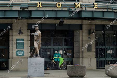 Al Jackson, a die-hard Seattle Mariners fan and 11-year season ticket holder, leans against the gate at the home plate entrance near the Ken Griffey Jr. statue at T-Mobile Park in Seattle, around the time when the Mariners' Opening Day baseball game against the visiting Texas Rangers would have started