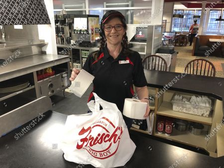 In this photo made, Frisch's Big Boy restaurant employee Nicole Cox bags up an order of toilet paper, among in-demand items including milk and bread the double-decker burger chain is now offering during the coronavirus outbreak in Cincinnati, Ohio. With business sinking under coronavirus outbreak restrictions,the nation's restaurants are transforming operations and menus to try to stay afloat