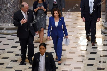 House Speaker Nancy Pelosi of Calif., center, walks with Rep. Dan Kildee, D-Mich., left, on Capitol Hill in Washington, . The House is working to pass a massive $2.2 trillion economic rescue bill that would cap Congress' tumultuous effort to rush the relief to a nation battered by the coronavirus