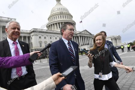 Rep. Thomas Massie, R-Ky., center, walking with Rep. Ken Buck, R-Colo., left, are followed by reporters as they leave Capitol Hill in Washington, . Massie attempted to slow action on a rescue package. Despite his effort, the House, acting with exceptional resolve in an extraordinary time, rushed President Donald Trump a $2.2 trillion rescue package Friday, tossing a life preserver to a U.S. economy and health care system left flailing by the coronavirus pandemic