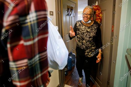 """Easter Brown, 77, of Washington, greets Michael Weber, with the nonprofit organization """"We Are Family DC,"""" as he delivers groceries to her apartment door, in Washington. Seniors are being encouraged to stay in their homes due to the risk of the COVID-19 coronavirus"""
