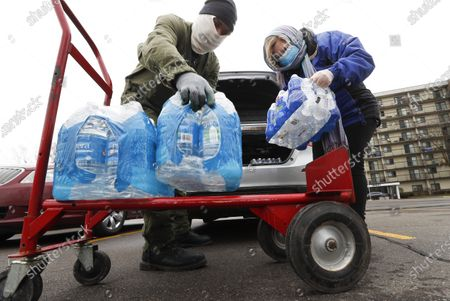 Rabbi Yosef Chesed, left, helps unload bottled water being donated from Lorie Lutz, right, at the Brightmoor Connection Food Pantry in Detroit, . The global coronavirus pandemic has brought water shutoffs in Detroit and in communities across the nation into sharp focus again amid a crucial time when officials are urging Americans to practice social distancing and basic hand-washing techniques to stop the spread of COVID-19