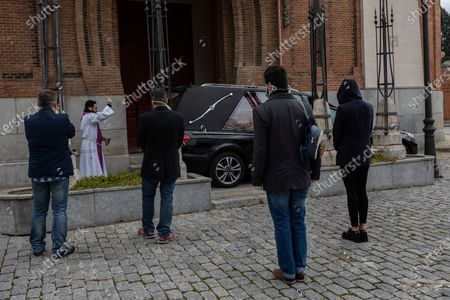 Priest Luis Miguel performs funeral rites at a Madrid cemetery during the coronavirus outbreak in Madrid, Spain, . The new coronavirus causes mild or moderate symptoms for most people, but for some, especially older adults and people with existing health problems, it can cause more severe illness or death