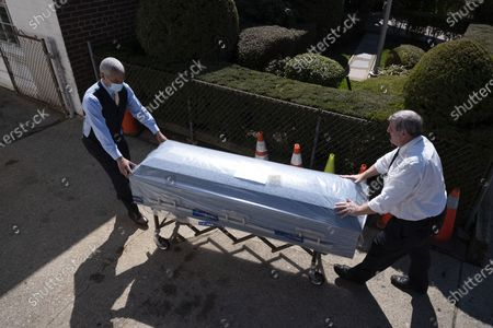 Omar Rodriguez, left, works with Joe Neufeld, the owner of the Gerard Neufeld Funeral Home, to move a newly delivered casket into the Queens business, during the coronavirus pandemic in New York. A funeral home in New York City has seen a steady stream of people who have died from the coronavirus. In just the past week, the funeral home has had services for almost a dozen people who have died, and is expecting more. For those mourning loved ones, funerals in the age of self-quarantine and social distancing are a far cry from the rituals of collective mourning that took place even a few weeks ago
