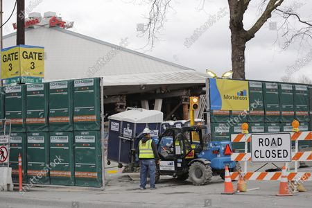 The massive roof of KeyArena is seen sitting atop temporary pillars behind fencing during a temporary halt in renovation of the arena into a much larger facility for the city's new National Hockey League team, in Seattle. Workers at the KeyArena construction site will be back on the job Monday, said Tim Leiweke, CEO of the Oak View Group, the company leading the $930 million arena renovation. The city now says that construction can go on as an exemption to the state-wide stay-at-home order so long as the contractor ensures workers maintain six feet of social distance and sanitizes their shared tools and workspaces