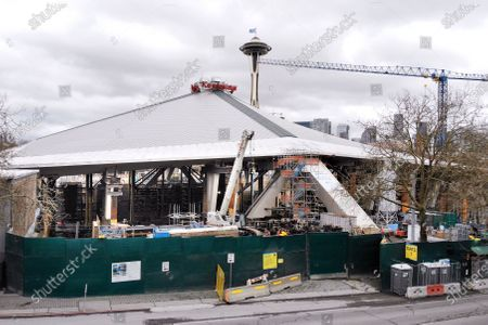 The massive roof of KeyArena is seen sitting atop temporary pillars during a temporary halt in renovation of the arena into a much larger facility for the city's new National Hockey League team, in Seattle. Workers at the KeyArena construction site will be back on the job Monday, said Tim Leiweke, CEO of the Oak View Group, the company leading the $930 million arena renovation. The city now says that construction can go on as an exemption to the state-wide stay-at-home order so long as the contractor ensures workers maintain six feet of social distance and sanitizes their shared tools and workspaces