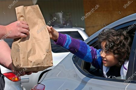 Stock Picture of Joseph Milligan, 9, reaches for the lunch delivered by Josh Leatherby at Leatherby's Family Creamery in Sacramento, Calif., . The family run ice cream parlor and restaurant has been providing curbside service for take out food since the orders banning dine in meals due to the coronavirus. There was a Friday special of free hot dogs for kids which prompted the visit by Joseph and his mother, Christina