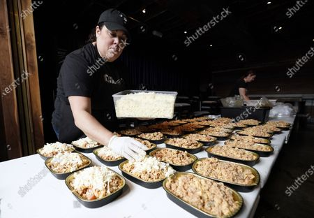 Stock Picture of Stephanie Velasco puts cheese on top of Lamburger Helper in take-and-bake containers at Georgia James restaurant, one of four restaurants owned by Houston chef Chris Shepherd, in Houston. Local officials have limited restaurants to takeout and delivery, a business environment that has become the temporary new normal for most eateries across the U.S. during the coronavirus outbreak