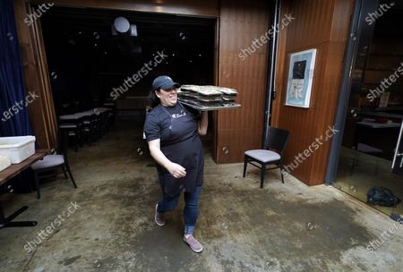 Stephanie Velasco carries a tray of food in take-and-bake containers at Georgia James restaurant, one of four restaurants owned by Houston chef Chris Shepherd, in Houston. Local officials have limited restaurants to takeout and delivery, a business environment that has become the temporary new normal for most eateries across the U.S. during the coronavirus outbreak