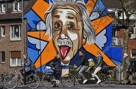 People pass an Albert Einstein graffiti on a sunny day, as Germany restricted public life due to the coronavirus outbreak in Muenster, western Germany, . In order to slow down the spread of the coronavirus, the German government allowed only two non-family members together in public. The new coronavirus causes mild or moderate symptoms for most people, but for some, especially older adults and people with existing health problems, it can cause more severe illness or death