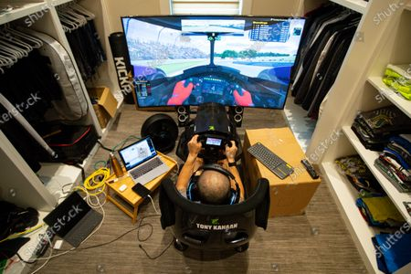 IndyCar driver Tony Kanaan, of Brazil, practices on his racing simulator in his home in Indianapolis, . Kanaan, along with other IndyCar drivers and NASCAR's Jimmie Johnson will compete in the series' inaugural virtual racing event Saturday