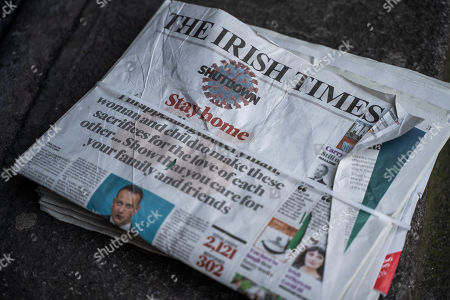 Uncollected stack of The Irish Times newspaper with 'stay home' announcement by Taoiseach Leo Varadkar on the first day of lockdown due to COVID-19