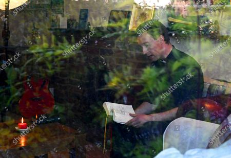 Shrubbery is reflected through glass as Reverend Peter Godden delivers a service to his congregation via the internet at his home the Clay Hill Vicarage in London, Britain, 29 March 2020. Britain's Prime Minister Boris Johnson has implemented social distancing measures banning social gatherings and groups of more than two people. People must stand more than two metres apart. Several European countries have closed borders, schools as well as public facilities, and have cancelled most major sports and entertainment events in order to prevent the spread of the SARS-CoV-2 coronavirus causing the Covid-19 disease.