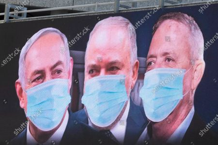 "Israeli Prime Minister Benjamin Netanyahu, left, Israeli Former Defense Minister and leader of the Yisrael Beiteinu (Israel Our Home) right-wing party Avigdor Lieberman, center, and Blue and White party leader Benny Gantz, are shown on a billboard wearing masks in the Israeli city of Ramat Gan, near Tel Aviv, . Gantz, Netanyahu's chief rival, was chosen on Thursday as the new speaker of parliament, an unexpected step that could pave the way to a power-sharing deal between the two men as the country grapples with a worsening coronavirus crisis. The billboard calling for unity reads: ""Benny, Avigdor and Bibi take off your masks, the people want unity"