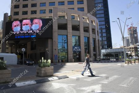 "Billboard shows Israeli Prime Minister Benjamin Netanyahu, left, Israeli Former Defense Minister and leader of the Yisrael Beiteinu (Israel Our Home) right-wing party Avigdor Lieberman, center, and Blue and White party leader Benny Gantz, wearing masks in the Israeli city of Ramat Gan, near Tel Aviv, . Gantz, Netanyahu's chief rival, was chosen on Thursday as the new speaker of parliament, an unexpected step that could pave the way to a power-sharing deal between the two men as the country grapples with a worsening coronavirus crisis. The billboard calling for unity reads, ""Benny, Avigdor and Bibi take off your masks, the people want unity"