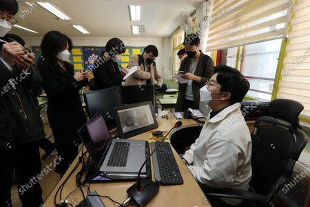 Reporters cover a pilot online lesson conducted by teacher Kim Hyun-soo from a classroom inside Yeongpoong Elementary School in Seoul, South Korea, 30 March 2020. The test is in preparation for another possible delay of the already-postponed re-opening of schools scheduled for 06 April amid the ongoing pandemic of the COVID-19 disease caused by the SARS-CoV-2 coronavirus.