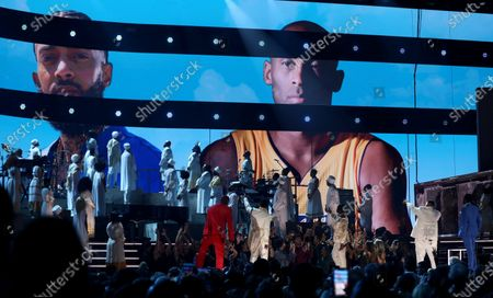 From left, John Legend, Kirk Franklin, DJ Khaled and Meek Mill point to a screen showing Nipsey Hussle and Kobe Bryant during a tribute at the 62nd annual Grammy Awards in Los Angeles. A year after Hussle's death, his popularity and influence are as strong as ever. He won two posthumous Grammys in January, he remains a favorite of his hip-hop peers and his death has reshaped his hometown of Los Angeles in some unexpected ways