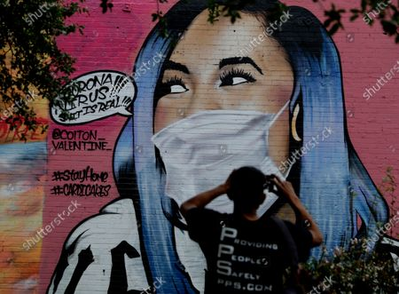 Stock Picture of Man photographs a mural of Cardi B that was updated by the artist to include a face mask to reflect the coronavirus pandemic, in San Antonio, . Due to the COVID-19 outbreak, San Antonio an many other Texas cities are under stay-at-home orders