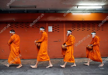 Thai Buddhist monks wear face shields to prevent the spread of COVID-19 disease caused by the SARS-CoV-2 coronavirus pandemic, during morning alms in Bangkok, Thailand, 31 March 2020. Buddhist monks from Bangkok's Wat Matchantikaram temple have produced their own face shields in an attept to protect themselfs against the spread of SARS-CoV-2.