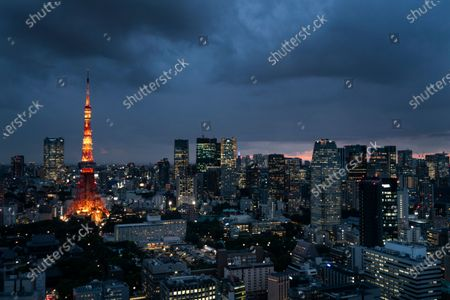 The Tokyo Tower is lit up at dusk as rain clouds hover over Tokyo's skyline. Patricia Espinosa, Executive Secretary of the United Nations Framework Convention on Climate Change, on Tuesday chided Japan over its new plan to reduce greenhouse gas emission. Environmental campaigners say Tokyo's new proposal shows no real ambition to increase existing efforts