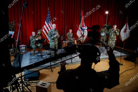 "Army Field Band members from left, Chief Warrant Officer 2 Kevin Pick, on the tuba, Master Sgt. Bradford Danho, on the clarinet, Staff Sgt. Andrew Emerich, on the drums, Sgt. 1st Class Jonathan Epley, on the banjo and Staff Sgt. Kyle Johnson, on the trombone, are spaced to allow for social distancing as they play during the rehearsal of their daily ""We Stand Ready"" virtual concert series at Fort George G. Meade in Fort Meade, Md., . The Army Field Band's mission is to bring the military's story to the American people. And they're not letting the coronavirus get in the way"