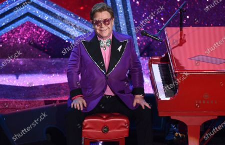 """Stock Image of Elton John appears after performing his nominated song, """"(I'm Gonna) Love Me Again,"""" at the Oscars in Los Angeles. The Elton John-led starry benefit concert that featured Billie Eilish, Mariah Carey and Alicia Keys on Sunday has raised nearly $8 million to battle the coronavirus. The musicians performed from their homes for the hour-long event that aired on Fox and iHeartMedia radio stations. The money will go to Feeding America and First Responders Children's Foundation"""