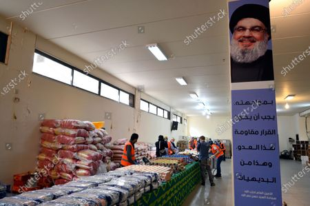 Hezbollah members prepare packages of food for needy people next to a banner bearing the photo of Hezbollah leader Hassan Nasrallah during a tour done by Hezbollah to show their preparation to fight the coronavirus and COVID-19 in the southern suburb of Beirut, Lebanon, 31 March 2020. According to the Lebanese health ministry, there are 463 registered cases of the COVID-19 disease caused by the SARS-CoV-2 coronavirus in the country as of 31 March 2020; twelve patients died, while 37 recovered. The curfew from 7:00 pm until 5:00 am local time was announced by authorities on 26 March 2020.